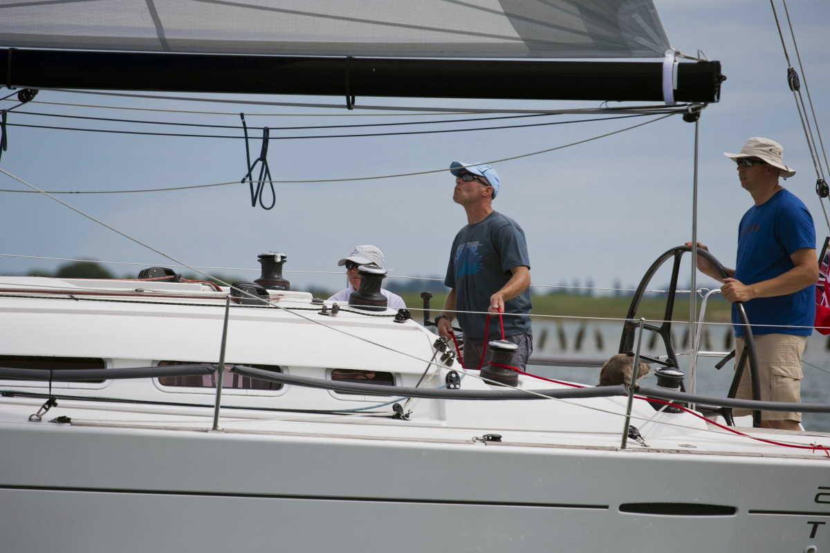Persona navegando el timón de un velero